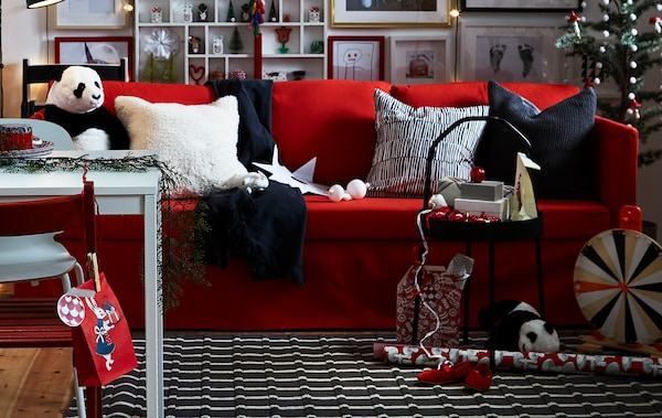 Un séjour mêlant le rouge, le noir et le blanc rempli de détails personnels et de mobilier flexible crée une ambiance chaleureuse et cosy.
