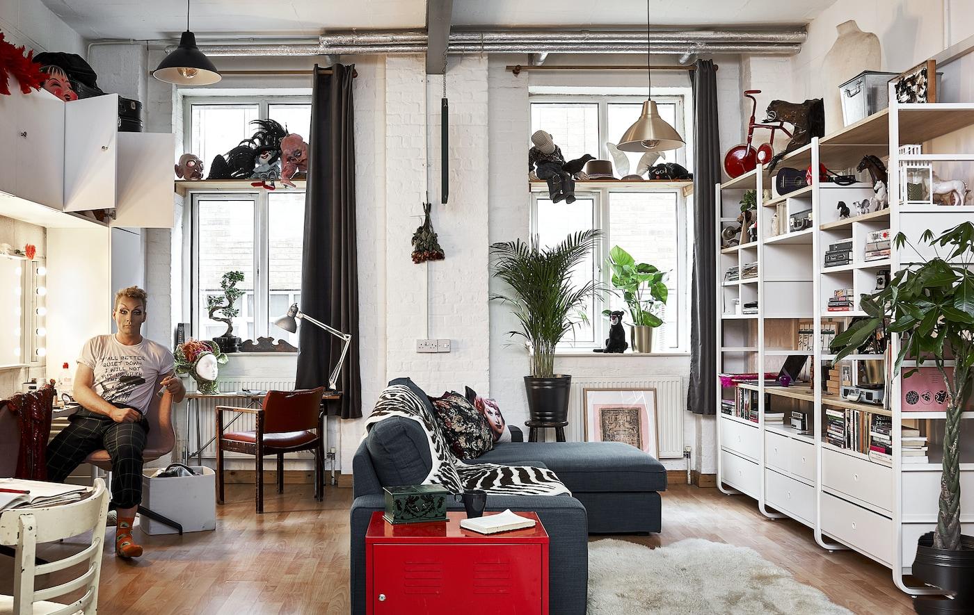 Un séjour ouvert avec des plafonds hauts, un canapé en forme de L, un rangement mural et Donald assis sur une chaise en face du miroir.