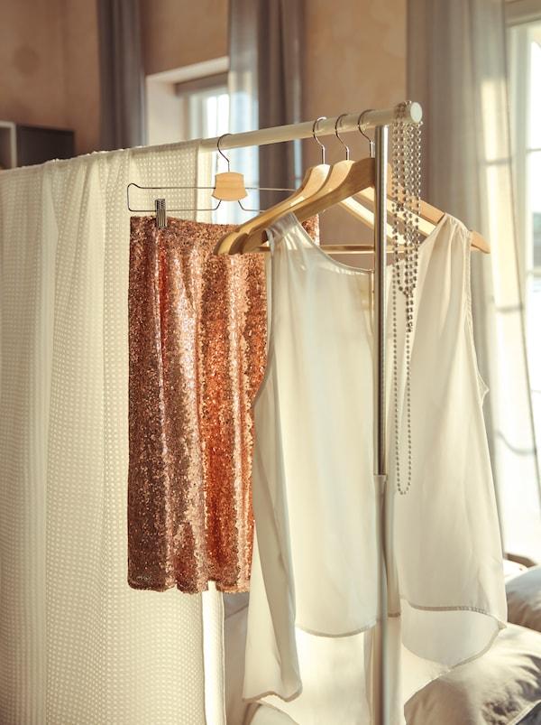 Un separator de cameră improvizat dintr-un suport de haine RIGGA și așternuturi VÅRELD folosite ca draperie, alături de umerașe cu haine de petrecere.