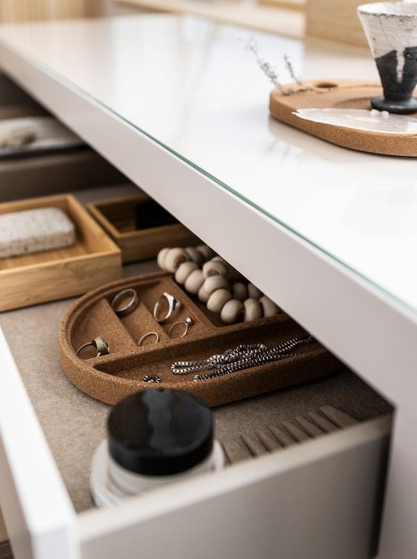 Un sertar lat, dar îngust al unei comode este lăsat întredeschis pentru a dezvălui bijuterii și accesorii de înfrumusețare, dintre care o parte se află în tăvi SAXBORGA.