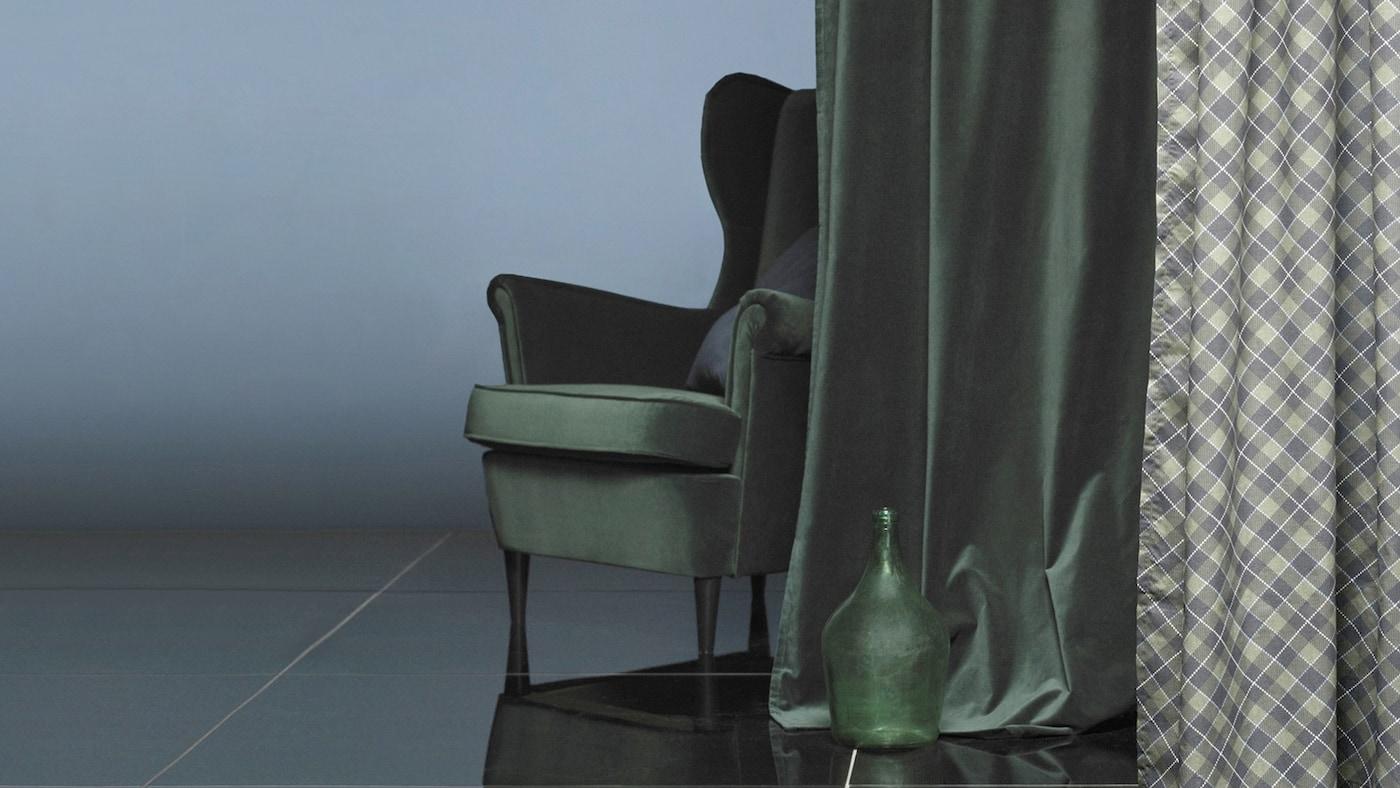 Un sillón detrás de una cortina en terciopelo verde oscuro a juego.