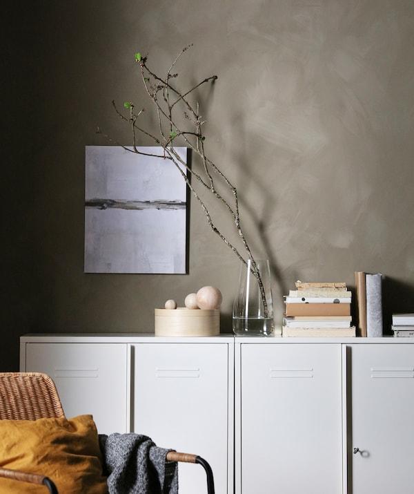 Un șir de corpuri albe pe un perete gri. Deasupra acestora se află cărți, decorațiuni, o vază cu o rămurică lungă cu muguri verzi.