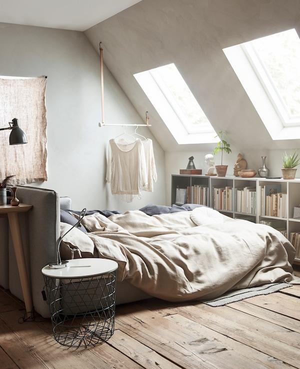 Un sofá cama abierto con ropa de cama de colores neutros.