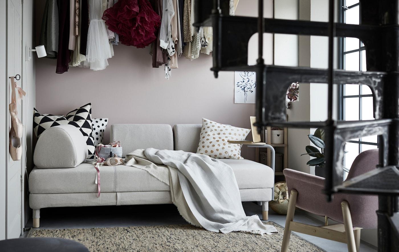 Un sofá cama IKEA FLOTTEBO en una habitación con una escalera de caracol y ropa colgando encima del sofá.