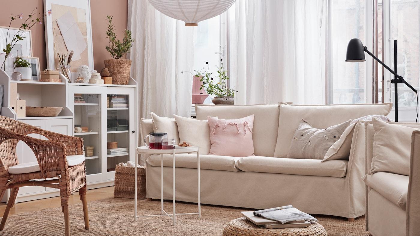 Un sofá de tres plazas, una alfombra plana, un sillón de ratán con un cojín, un armario con puerta de vidrio y un armario con dos puertas.