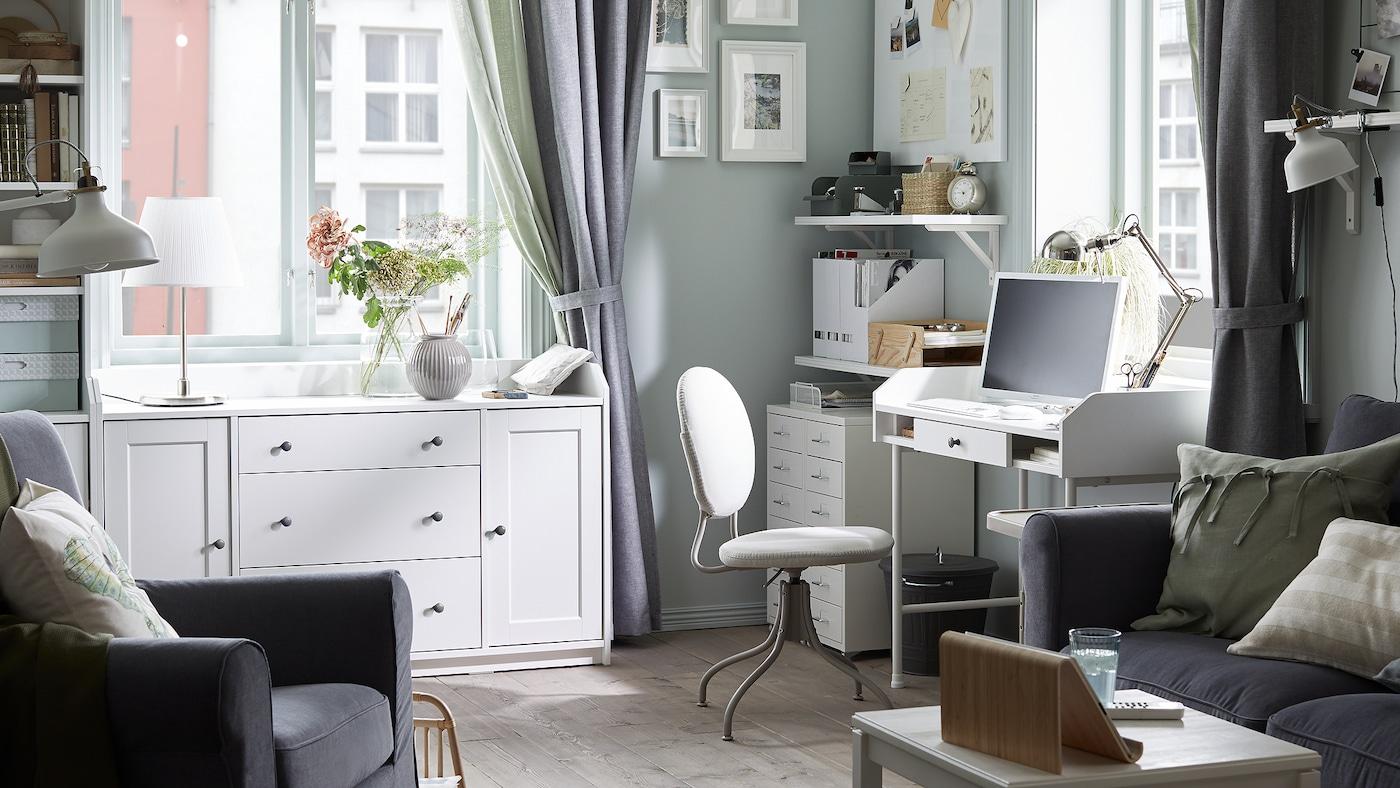 Un sofá gris oscuro, un escritorio blanco con un ordenador, una silla giratoria beige, estantes blancos con documentos y armarios blancos.