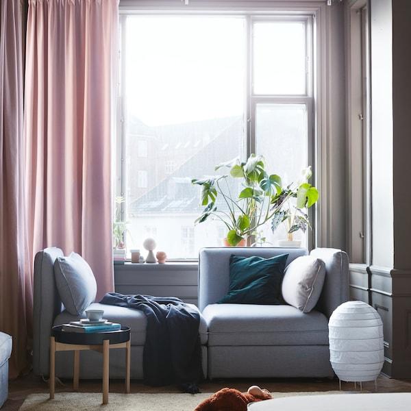Un sofá modular biplaza gris con almacenaje IKEA VALLENTUNA al lado de una gran ventana con cortinas de color rosa.