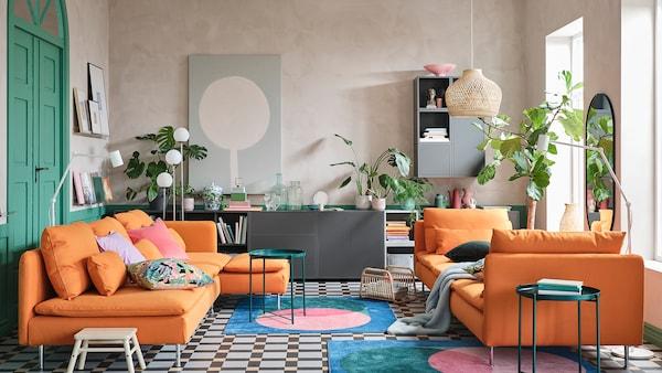 Un soggiorno con divano e chaise-longue arancioni, una combinazione di mobili grigi, tappeti colorati e tavolini vassoio verdi.