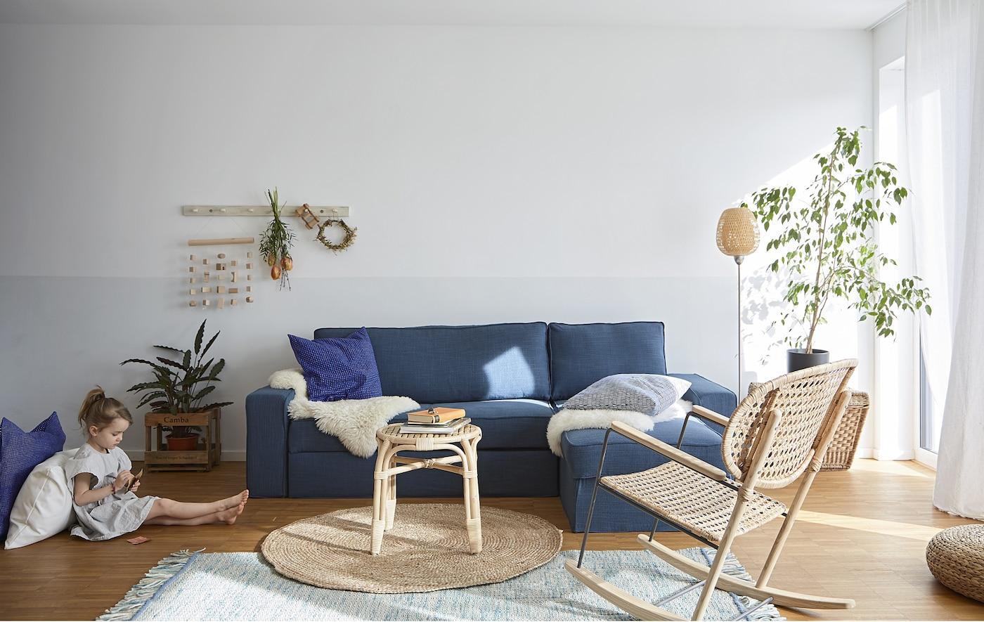 Un soggiorno con divano letto blu e mobili in rattan - IKEA