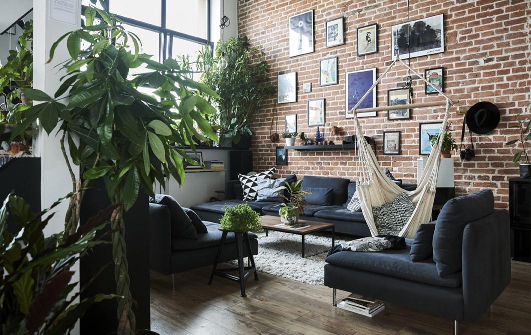 Un soggiorno con i soffitti alti, una parete con mattoni a vista e un divano componibile grigio – IKEA