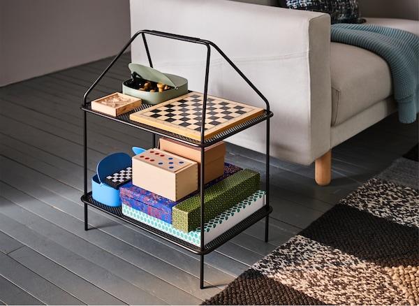 Un soporte de revistas IKEA YPPERLIG negro junto a un sofá de color crema, repleto de juegos de mesa.