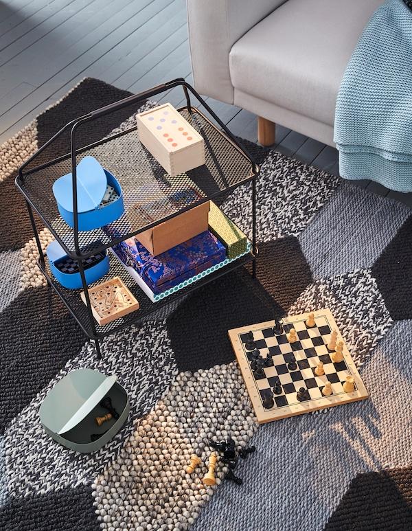 Un soporte de revistas IKEA YPPERLIG negro utilizado para colocar juegos de mesa sobre una alfombra negra y gris.