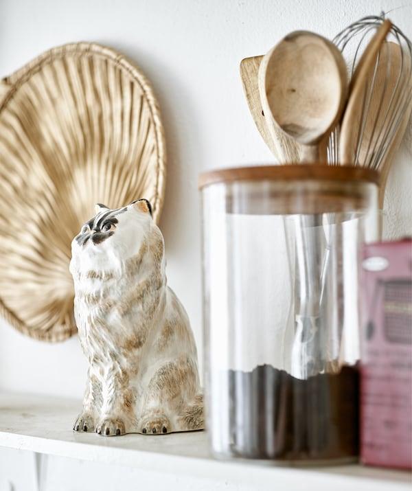Un soprammobile a forma di gatto, utensili da cucina in legno e un barattolo di caffè su una mensola – IKEA