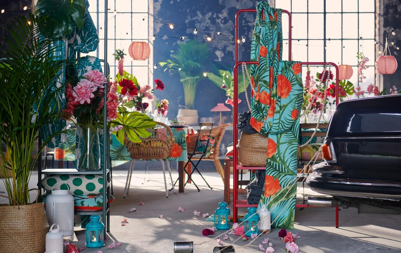 Un spacieux intérieur de style industriel aménagé pour une fête, avec textiles, décorations, plantes et la carrosserie arrière d'une voiture à laquelle sont attachées des boîtes de conserve.