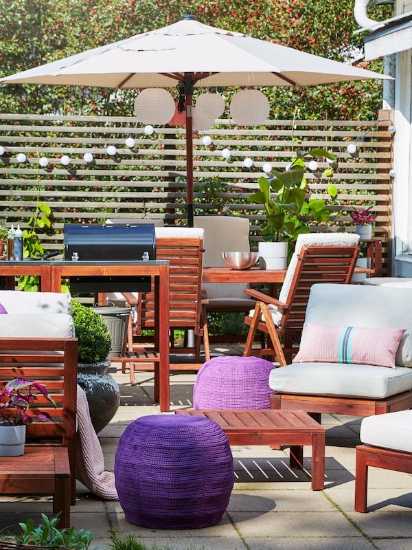 Un spațiu în aer liber mobilat cu mese, scaune și o umbrelă de soare, cu perne și pufuri și ghirlande luminoase.