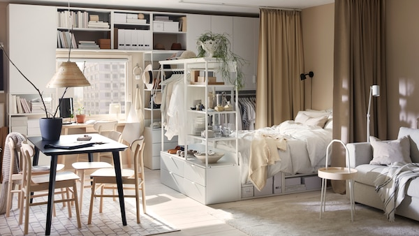 Un studio în care se află diferite combinații cu soluții de depozitare PLATSA și un cadru de pat alb, o masă de sufragerie și perdele bej.