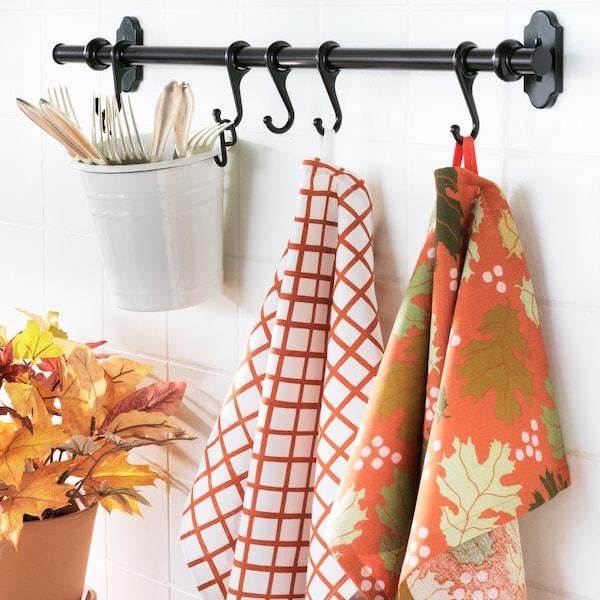 Un support de cuisine avec des ustensiles et des serviettes orange.