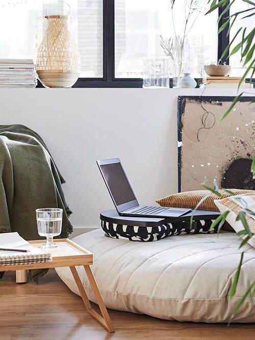 Un support pour ordinateur portable noir et blanc, avec un ordinateur portable dessus, un pouf recouvert d'étoffe écrue, un plateau, un verre d'eau, un carnet.