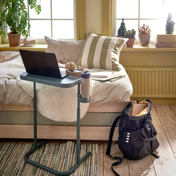 Un support pour ordinateur portable turquoise placé devant un lit utilisé comme fauteuil. Un sac à dos gris se trouve à côté du lit.