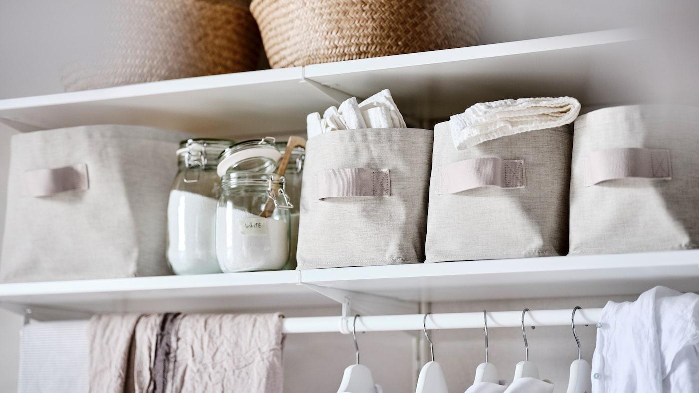 Un système de rangement BOAXEL avec des étagères blanches, des bocaux en verre contenant de la lessive en poudre et des boîtes de rangement PURRPINGLA.