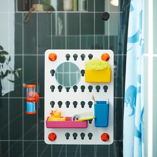 Un taboleiro con 6 recipientes de cores variadas e cun reloxo de area laranxa con area azul están adheridos a unha porta de cristal para a ducha.