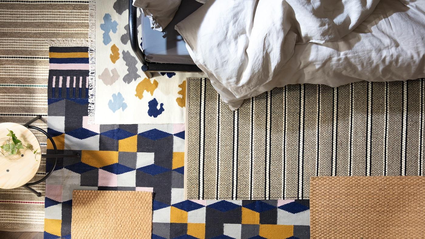 Un tabouret et le bord d'un litFYRESDAL sur le sol, avec de nombreux tapis de différents motifs superposés.