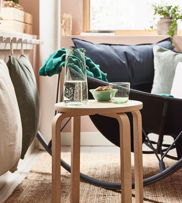 Un taburete de madera FROSTA utilizado como mesa auxiliar en un agradable salón.