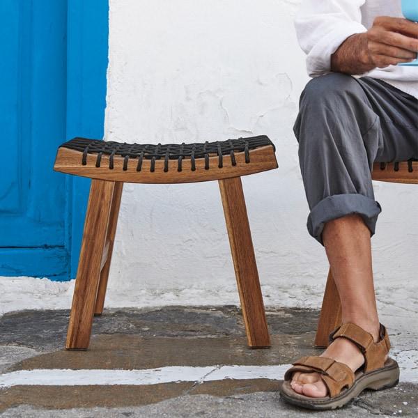 Un taburete STACKHOLMEN marrón claro de resistente madera de acacia con un asiento de cuerda negra trenzada, ligeramente curvada hacia arriba.