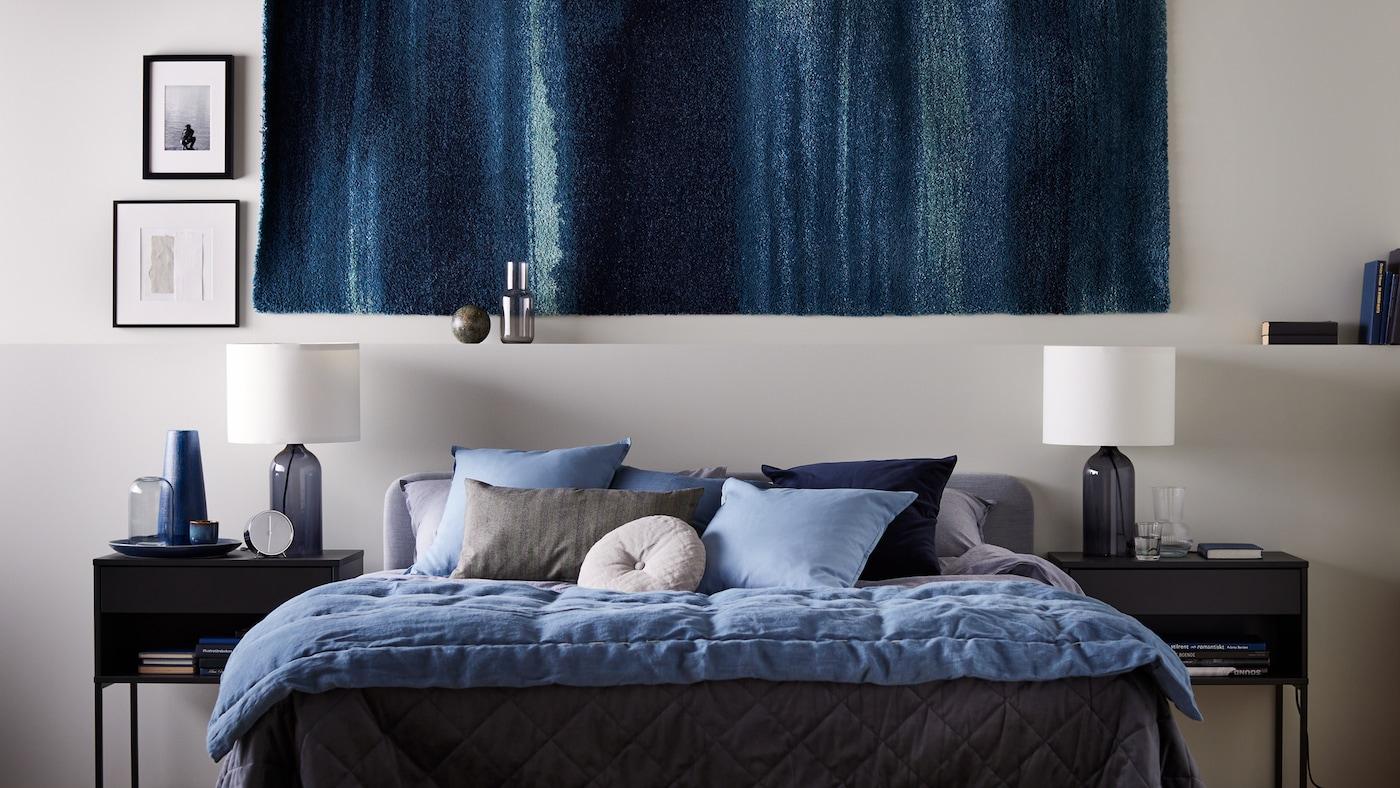 Un tapis au mur, avec des tables de chevet VIKHAMMER de part et d'autre d'un lit double SLATTUM gris clair, avec des draps KOPPARBLAD.