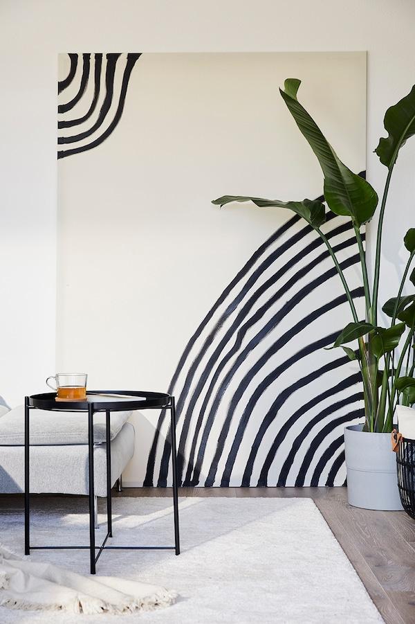 Un tapis beige avec des lignes noires décorant un mur.