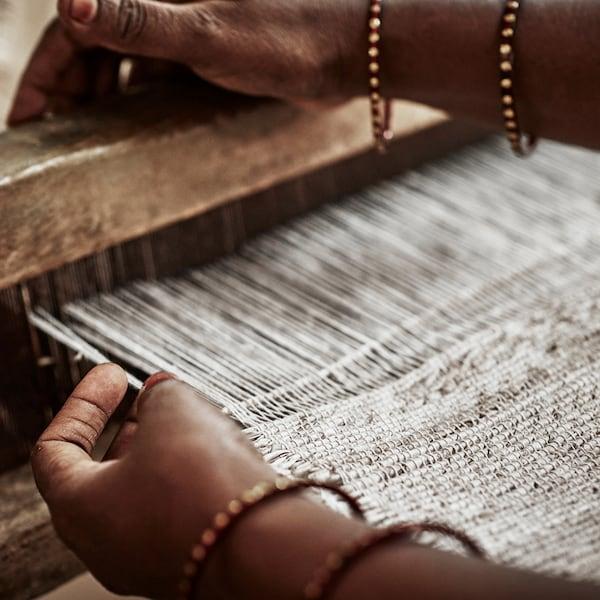 Un tapis en cours de tissage, les mains du travailleur passant le fil dans le métier à tisser.