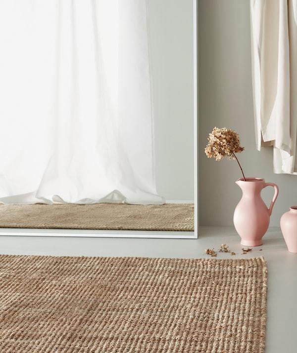 Un tapis en jute sur un plancher gris, un vase rose contenant une fleur séchée près d'un grand miroir blanc où se reflète un rideau blanc.