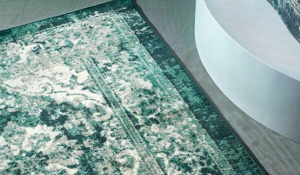 Un tapis vert VONSBÄK au look vintage usé posé sur un sol gris-vert.