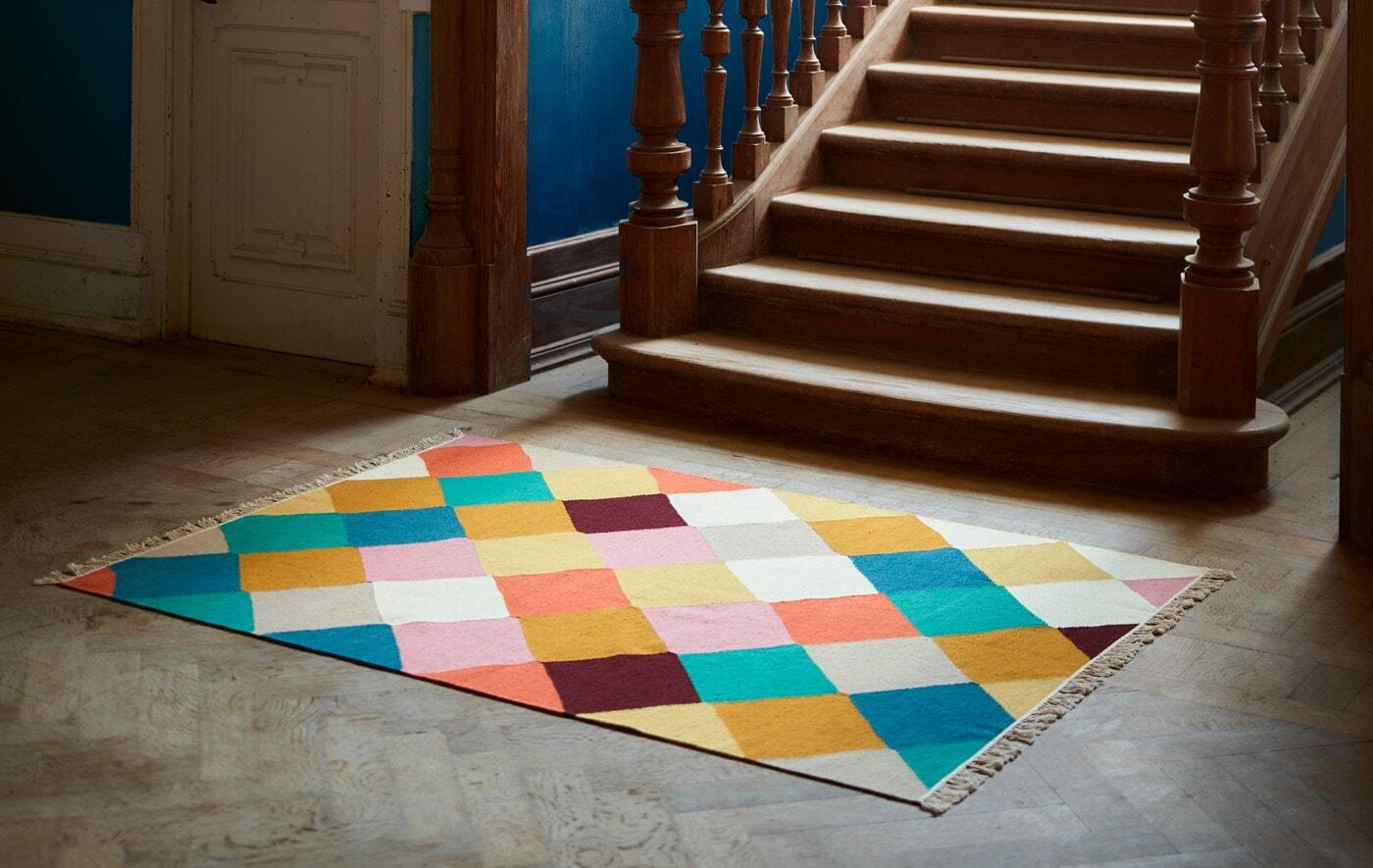 Un tapis VINDERÖD à motifs à carreaux multicolores se trouve au pied d'un escalier en bois sombre doté d'ornements élaborés.