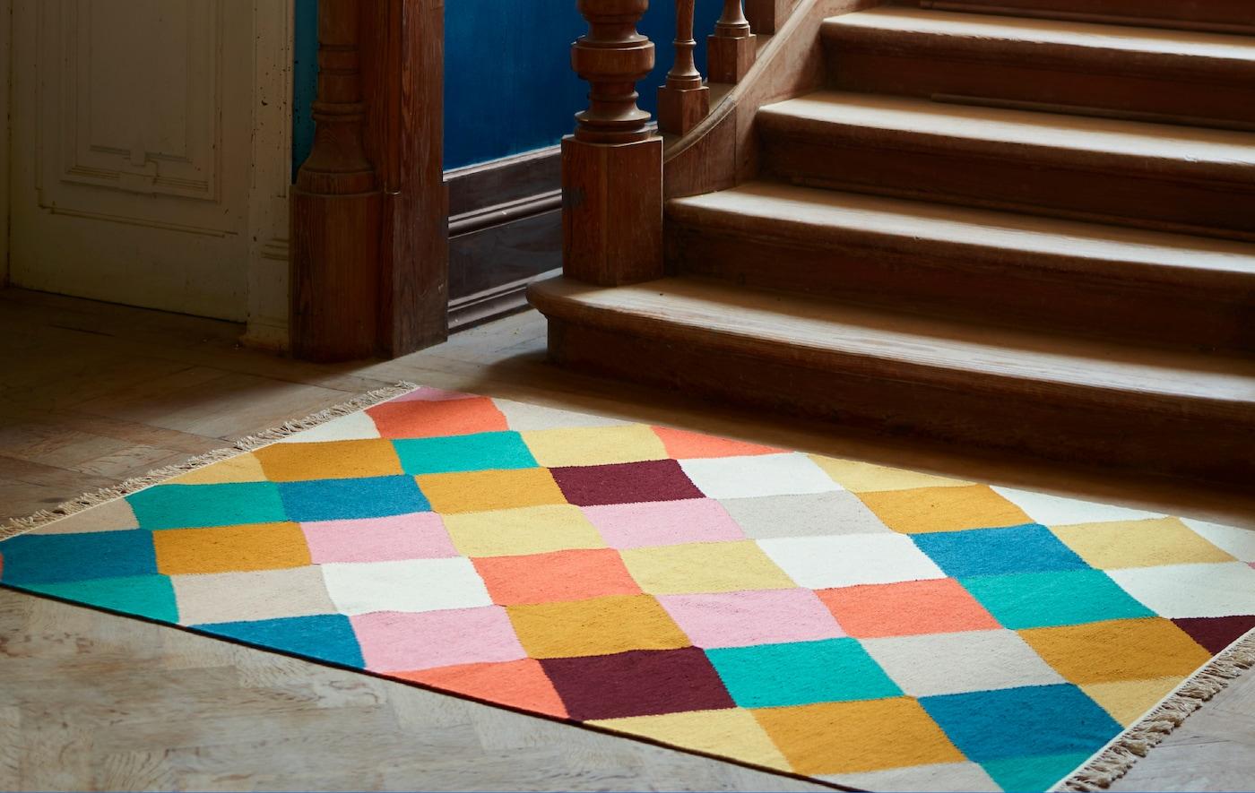 Un tapis VINDERÖD avec un motif à carreaux multicolores au pied d'un escalier en bois foncé avec une rampe ouvragée.