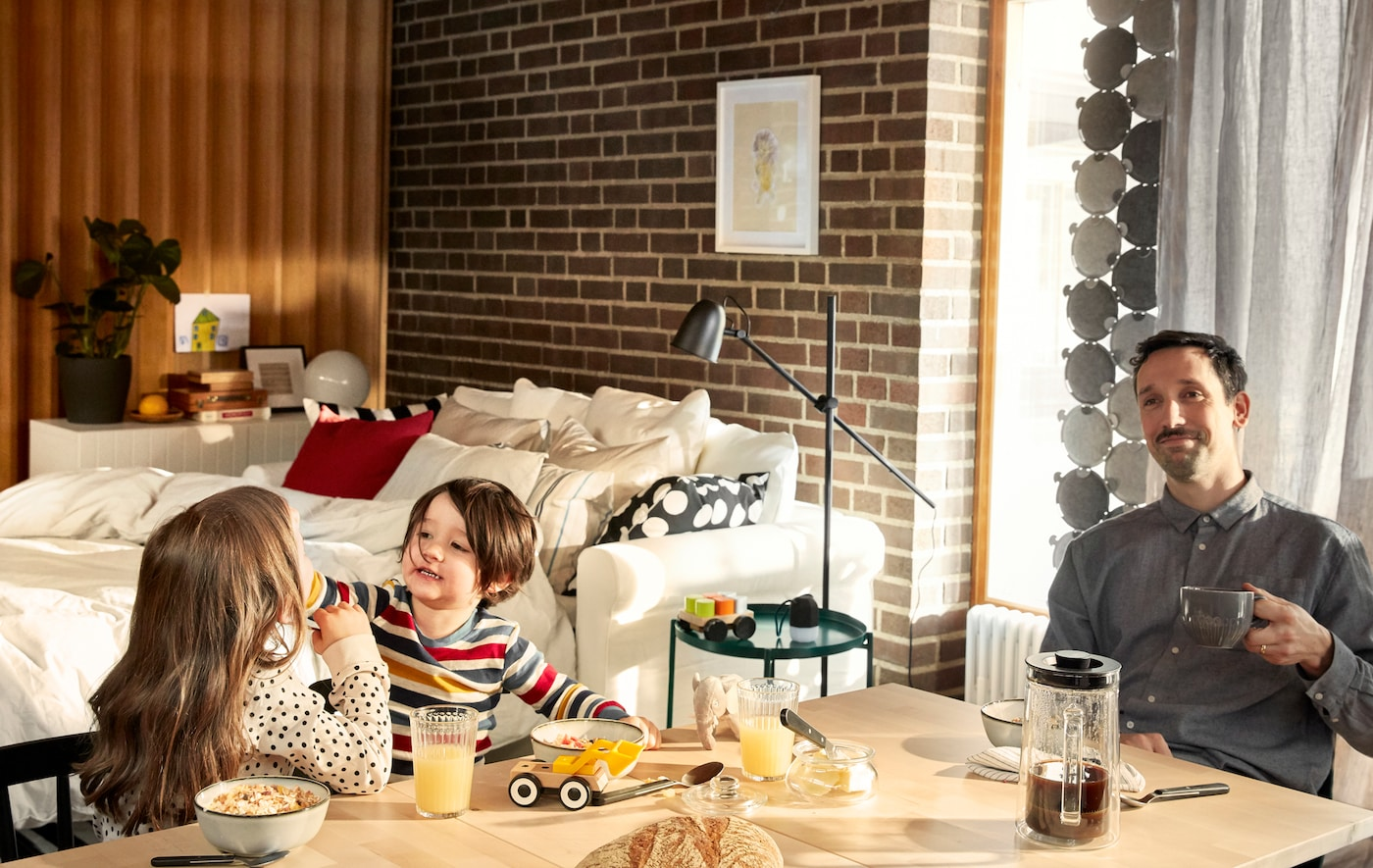 Un tată relaxat la masa unde se servește micul dejun își savurează cafeaua în timp ce cei doi copii ai săi se joacă cu mâncarea lângă el.