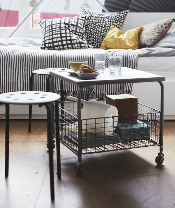 Un tavolino con rotelle e cestello contenitore, due piccoli sgabelli e un letto divano – IKEA