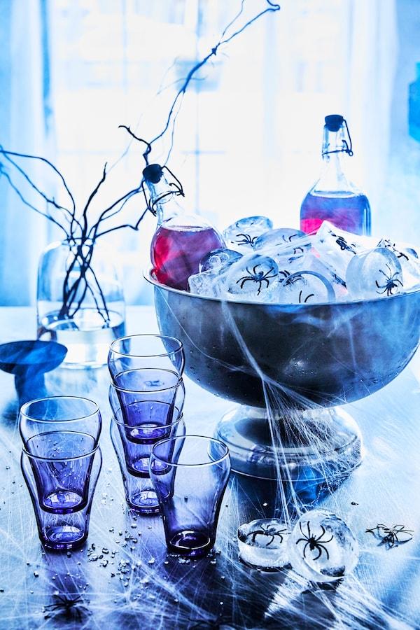 Un tavolo ispirato a Halloween, con bevanda al mirtillo rosso in bottiglie KORKEN con tappi in una grande ciotola con cubetti di ghiaccio con ragni di plastica al loro interno, seduti su un tavolo con tazze e ragnatele.