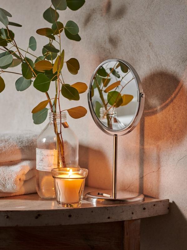 Un teanc de prosoape, o lumânare VÄLDOFT și o sticlă cu o crenguță de frunze de eucalipt pe o etajeră într-o baie rustică.