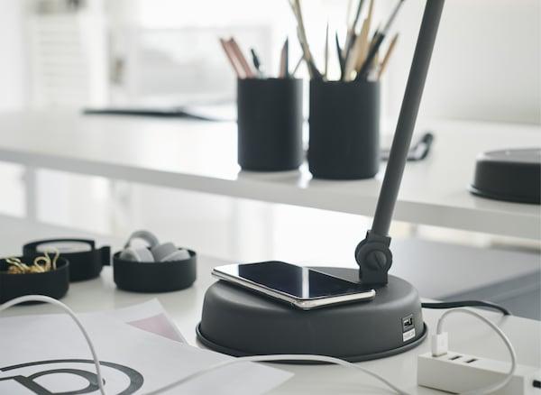 Un téléphone est posé sur la base d'une lampe de bureau gris foncé, elle-même posée sur un bureau blanc.