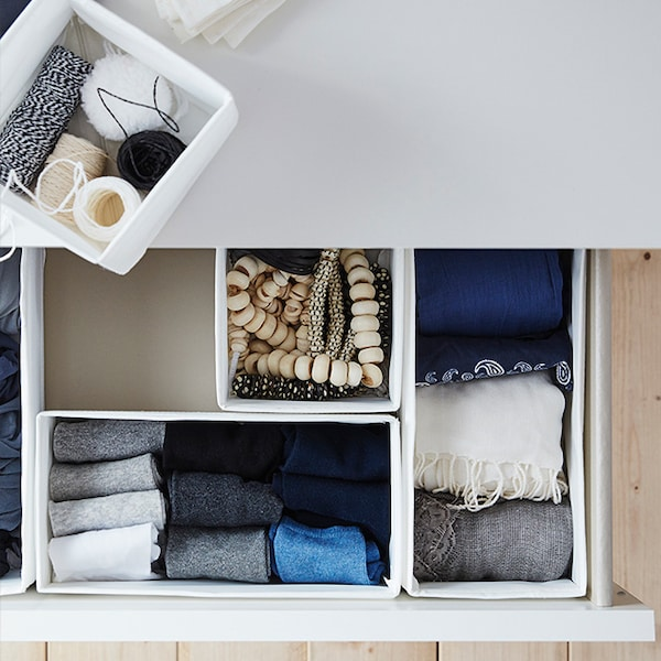Un tiroir de table de chevet est ouvert. À l'intérieur se trouvent des boîtes de rangement blanches avec des chaussettes bien pliées et des accessoires.