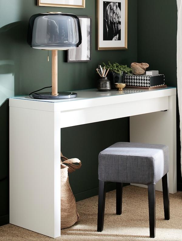 Un tocador blanco, una lámpara de mesa gris, un taburete gris y negro y marcos dorados.