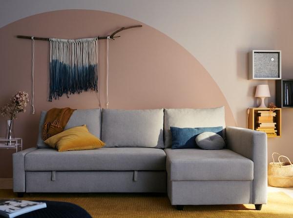 Un trois-places gris devant un mur avec un demi-cercle rose et une œuvre d'art textile.