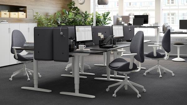 Un ufficio arredato nei toni del nero e del grigio, con scrivanie regolabili in altezza BEKANT, in marrone-nero, posizionate una di fronte all'altra in modo da delimitare gli spazi di lavoro.