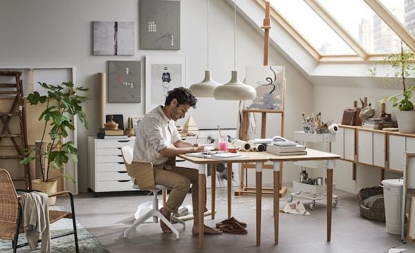 Un uomo disegna nello studio che ha creato nella sua casa, usando tavoli ed elementi contenitori di IKEA.