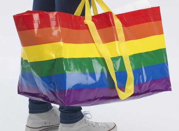 Un uomo in jeans e scarpe da ginnastica bianche, con una borsa FRAKTA nei colori dell'arcobaleno – IKEA