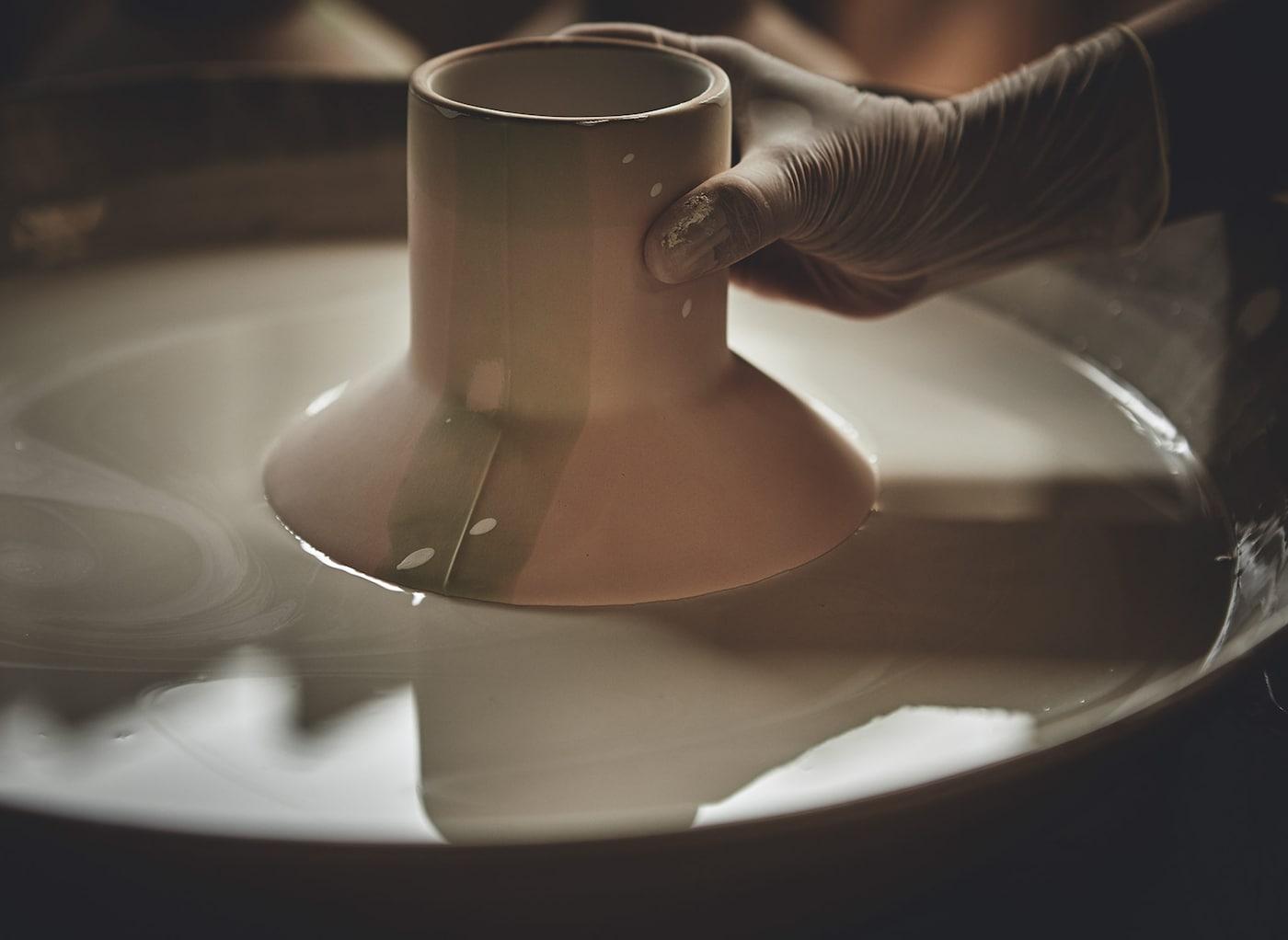 Un vase en céramique fait main de la collection HANTVERK de IKEA occupé à être vitrifié à la main par immersion dans un bain.