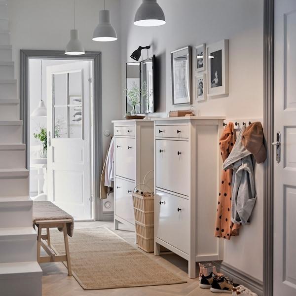 Un vestíbulo branco con dous zapateiros HEMNES brancos de estilo tradicional e unha ringleira de ganchos para colgar abrigos.