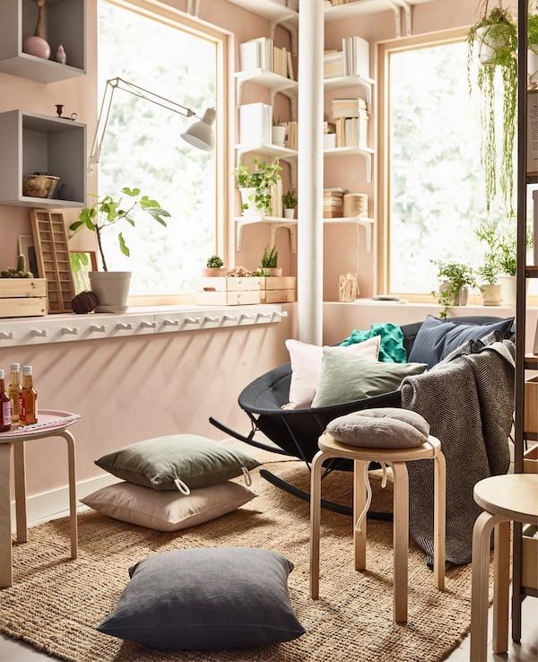 Un zona de asientos mixta creada sobre una alfombra de yute plana LOHALS en un salón rosa.