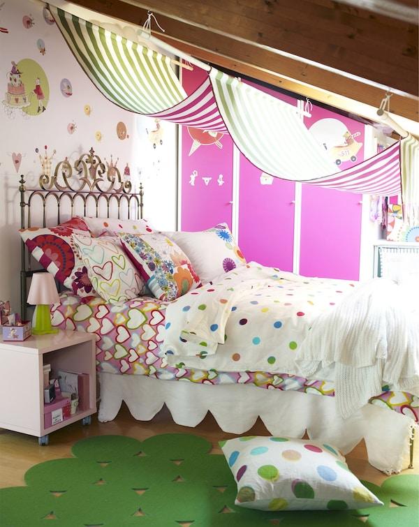 Una agradable cama infantil con cabecero metálico y una mezcla de coloridos estampados en las almohadas y funda nórdica.